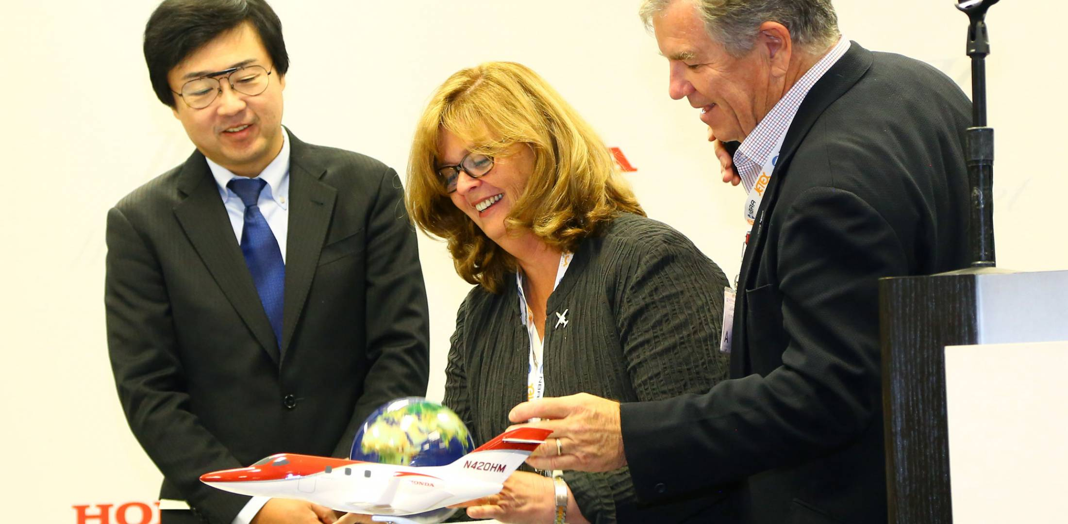 """Honda Aircraft founding president and CEO Michimasa Fujino, left, helps hoteliers Kim, center, and Julian MacQueen celebrate the completion of their """"Around the World in 80 Stays"""" tour. The couple circumnavigated the globe in their new HondaJet. PHOTO: DAVID McINTOSH"""