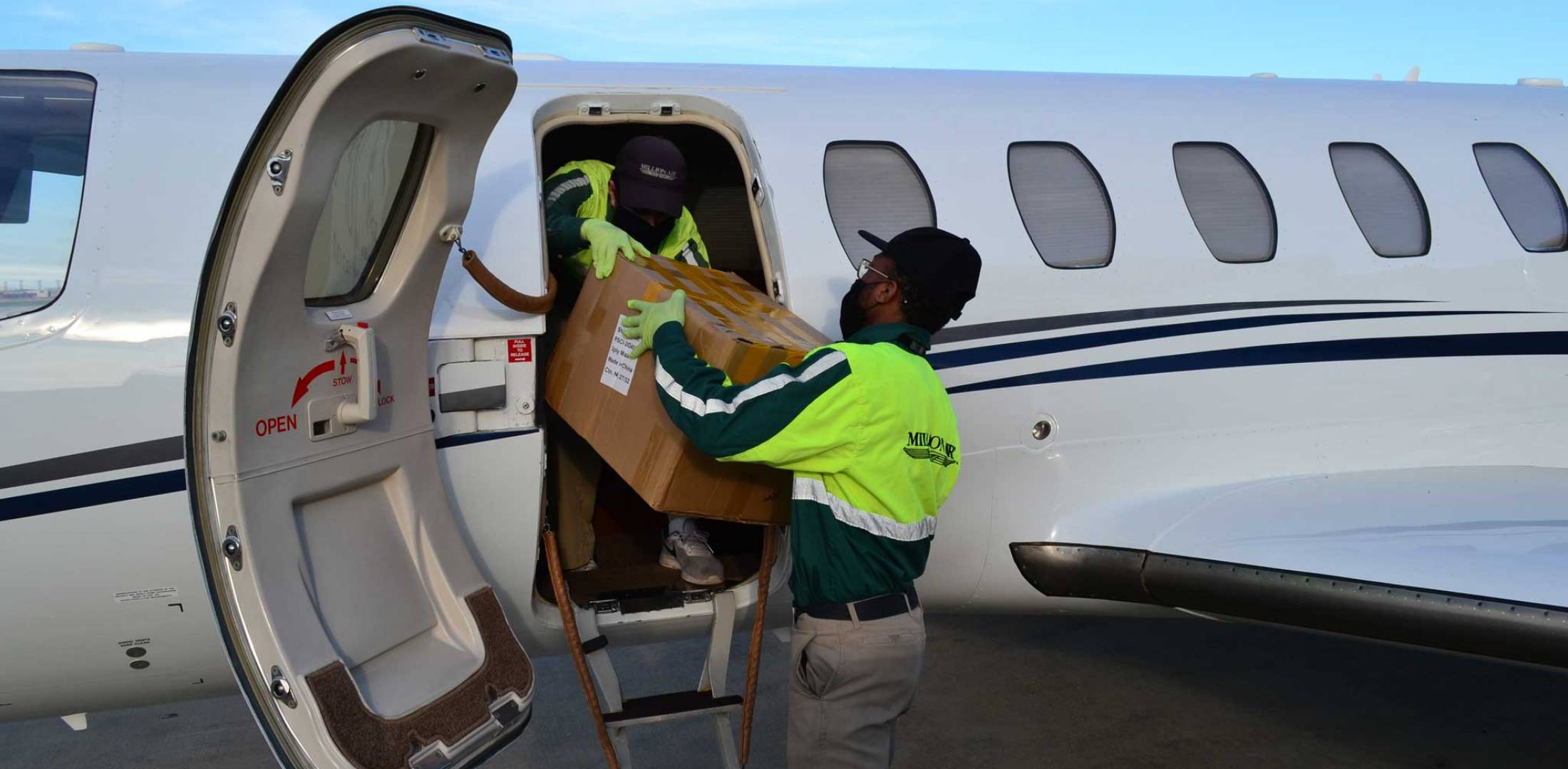 Loading donated boxes of masks aboard business jet