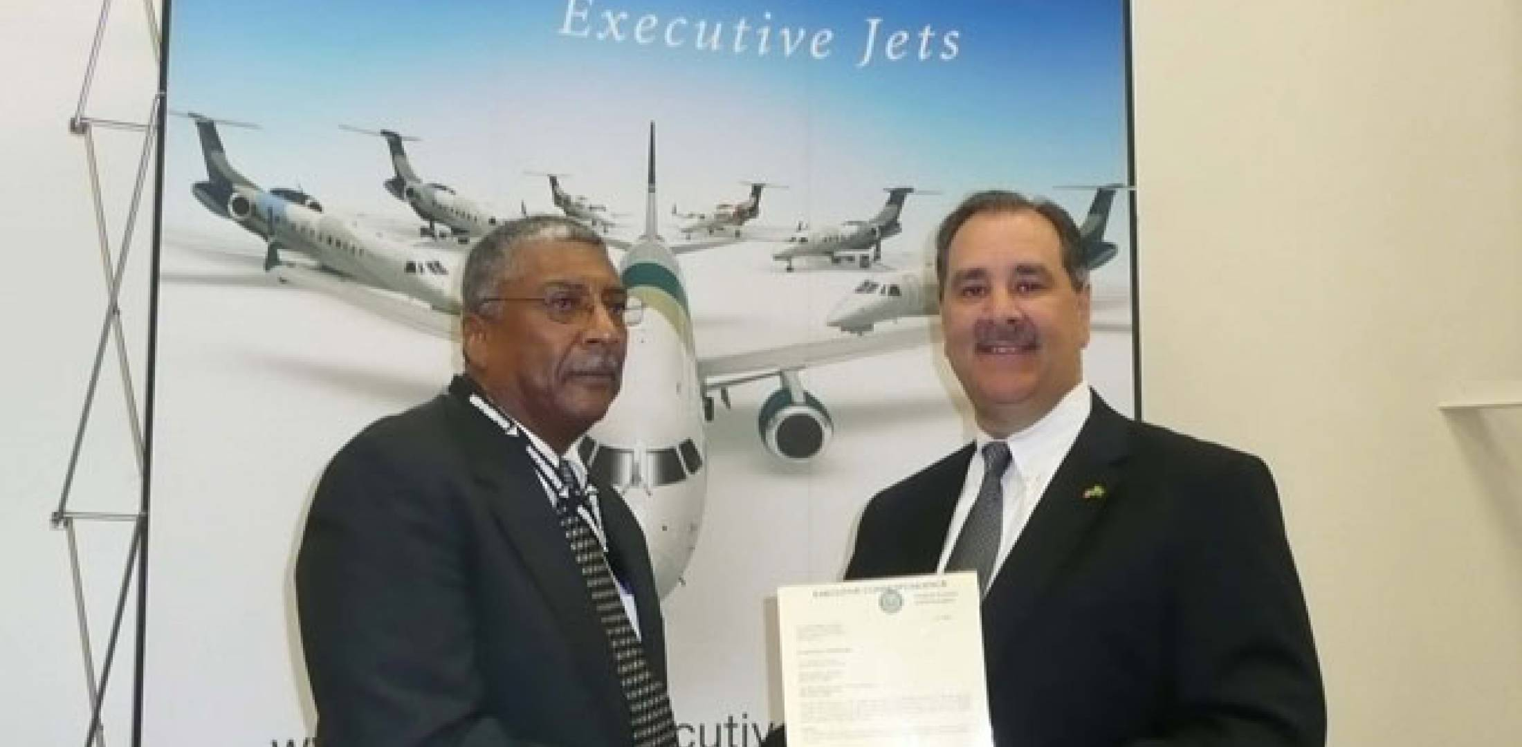 (L-R): Mack Riley, manager of the FAA's Orlando manufacturing inspection district office, hands the production certificate for Embraer's Melbourne Phenom 100 assembly line to Phil Krull, managing director of Melbourne production, during ceremonies on June 18