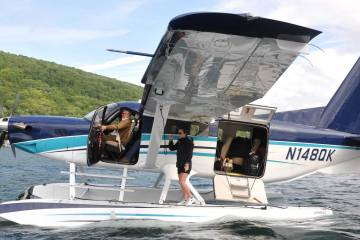 seaplane in water with pilot and woman walking on floats