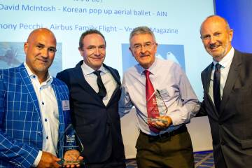 4 men standing together and one holding an award