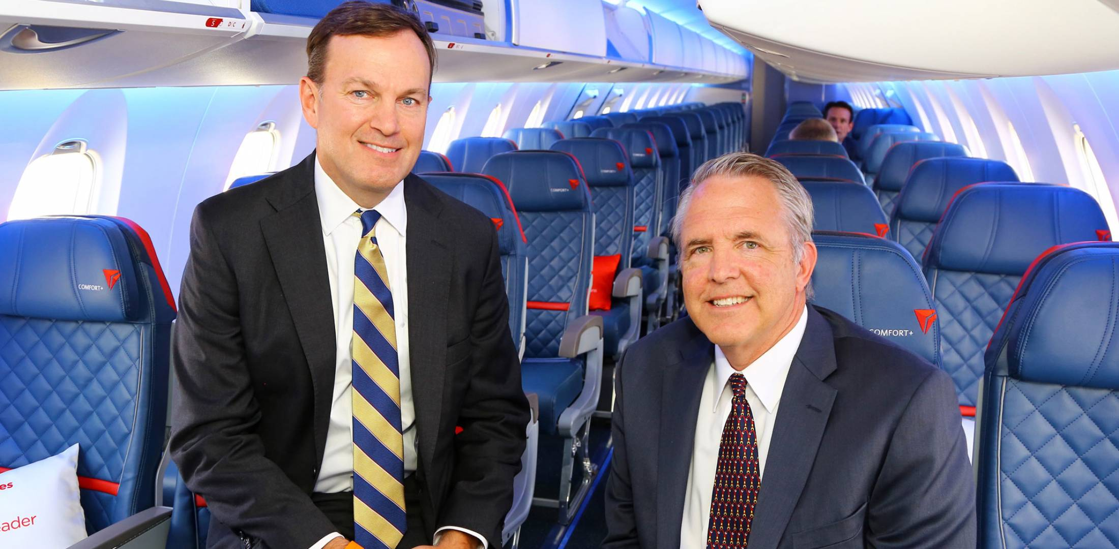 two men sitting in an aircraft cabin