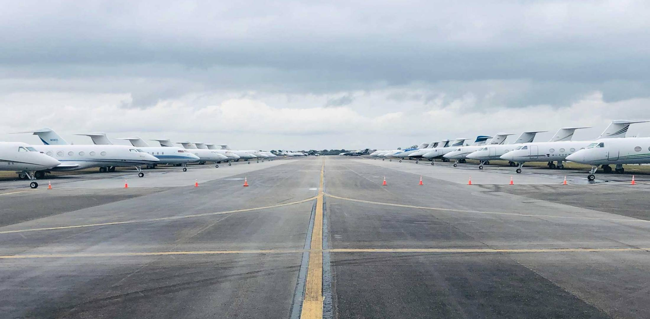 Private jets line a runway used for overflow parking at Miami Opa-locka Executive Airport