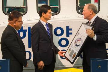 Sikorsky sales representative Sam Chae, Korea Coast Guard senior inspector Seong Chul Kim and Sikorsky president Dan Schultz mark the second S-92 going to the service. The aircraft on display at Sikorsky's booth will officially be handed over to the coast guard following Heli-Expo.