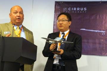 Cirrus's John Duplaise (left) presented an SR22 model to John Fang of China's Juhe Aviation