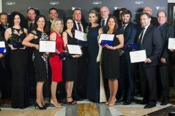 group of people holding awards