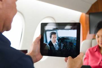 man and woman looking at mobile devices inside of aircraft