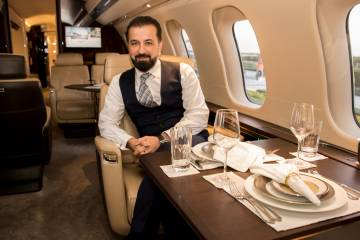 man sitting in business jet cabin