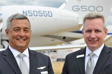 2 men standing in front of airplane