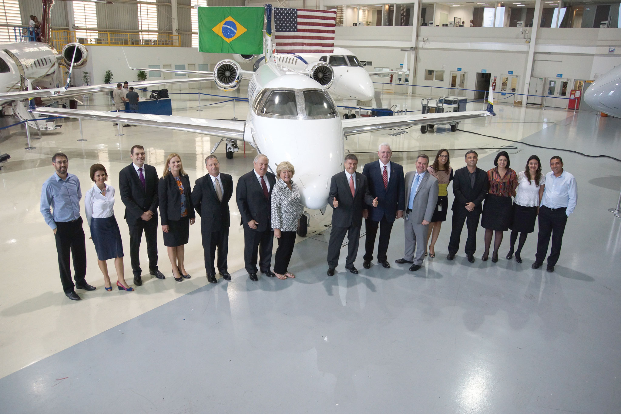 Embraer Executive Jets president and CEO Marco Túlio Pellegrini (center  right) and company employees, celebrated delivery of the 30th Phenom with  Executive ...