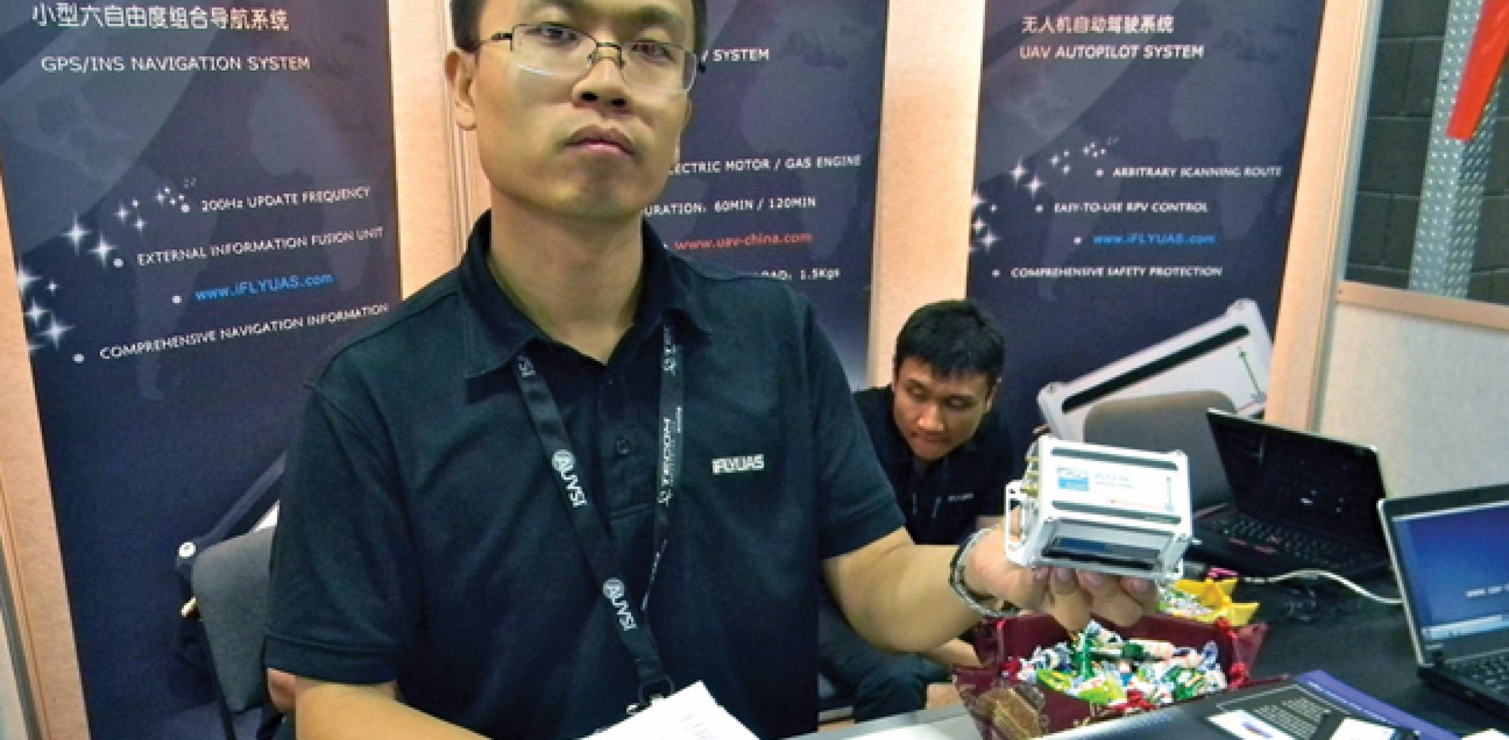 Li Xiaoyu, iFlyUAS general manager, displays the miniature autopilot used in the Chinese Creaton T10 unmanned aircraft system.
