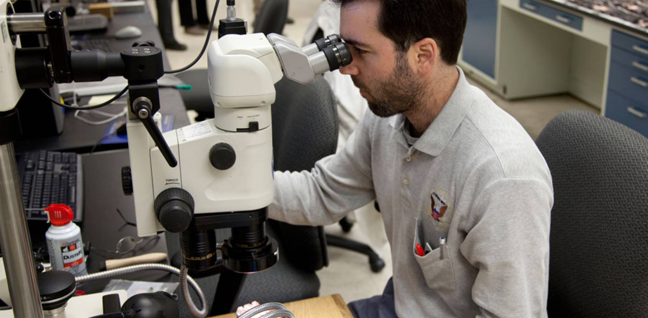 NTSB investigator Joseph Panagiotou uses a stereo microscope to examine a battery cell from the JAL Boeing 787 that caught fire on January 7. (Photo: NTSB)