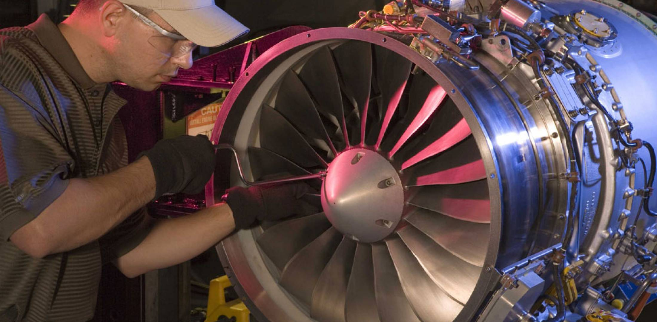 A Dallas Airmotive engine technician completes final installation of a PW500 spinner.