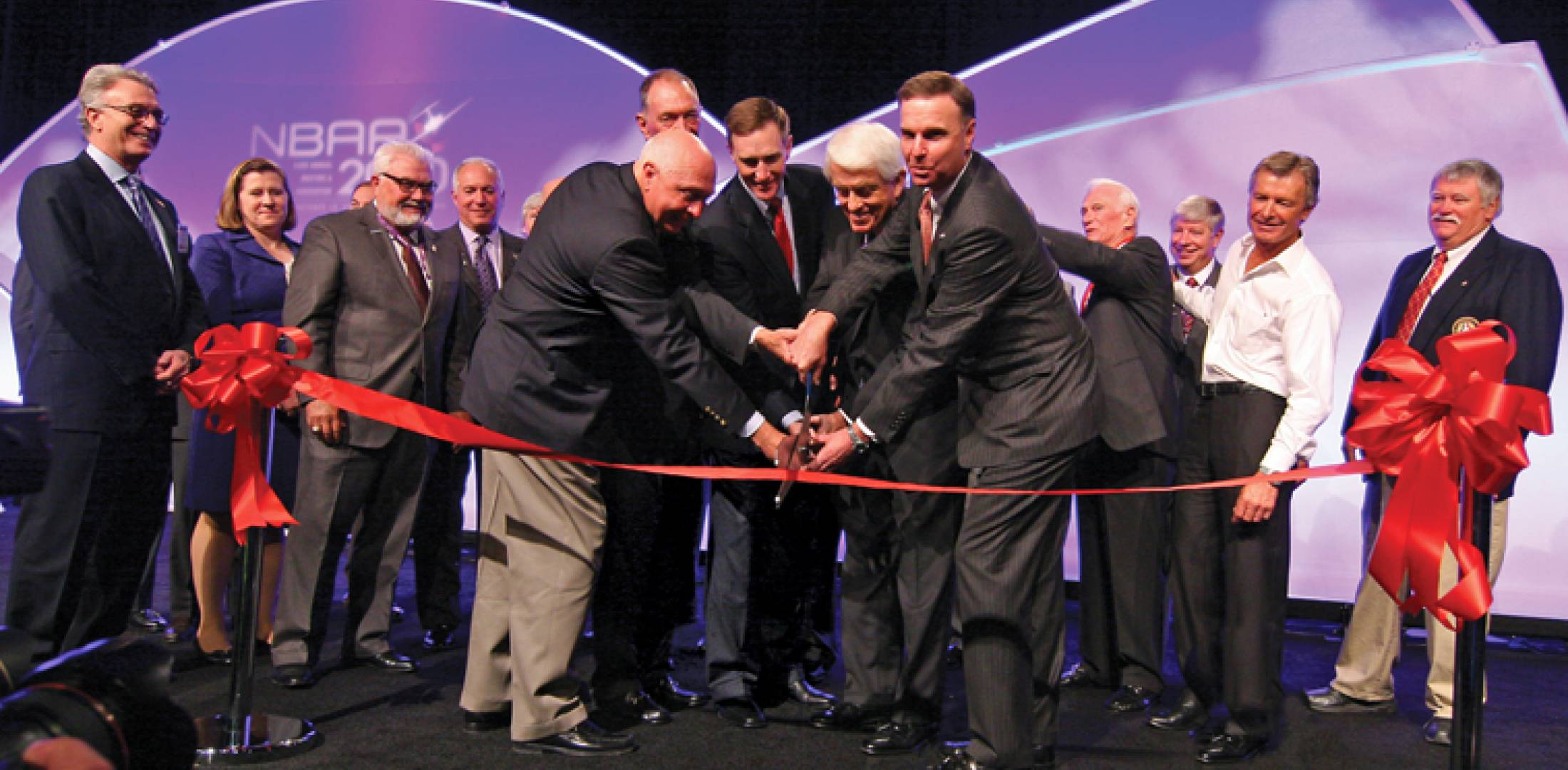 Handling the ribbon-cutting for NBAA are (l to r)  Jimmy Hayes, Cox Enterpris...