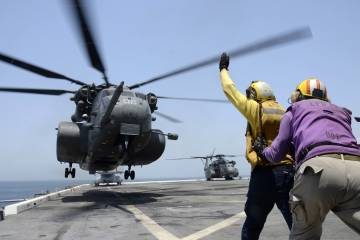 An MH-53E Sea Dragon lands on the deck.