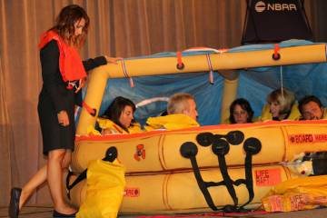 conference attendees in life raft on stage
