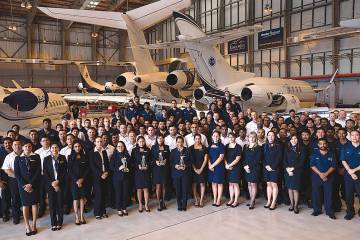 ExecuJet Middle East team gathered in airplane hangar.