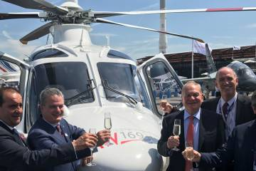 men with champagne in front of helicopter