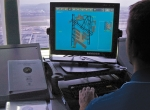 An air-traffic controller monitors an ASDE-X display of aircraft movements on...