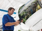 Mechanic working on aircraft, using iPad as resource