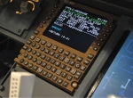 A multifunction control display unit in aircraft cockpit shows a controller-pilo
