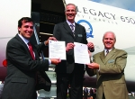 Displaying the appropriate paper work are (l to r) Embraer vice presidents Cl...